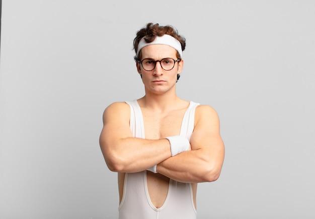 Humoristische sportman voelt zich ontevreden en teleurgesteld, ziet er serieus, geïrriteerd en boos uit met gekruiste armen