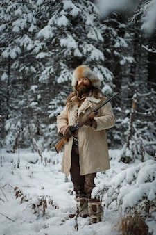 Hunter man in winter warme vintage kleding met pistool in winter forest