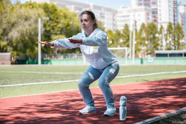 Hurkende jonge schoonheid meisje doet oefeningen in het stadion