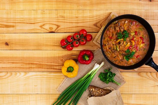 Hutspot met vlees en groenten in tomatensaus op houten. bovenaanzicht