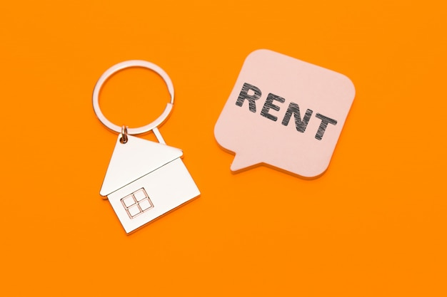 Huur concept. metalen sleutelhanger in de vorm van een huis en een sticker met de inscriptie - huur op een oranje achtergrond.