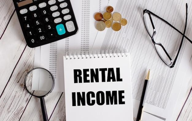 Huur inkomen geschreven in een wit notitieblok naast een rekenmachine, contant geld, bril, een vergrootglas en een pen