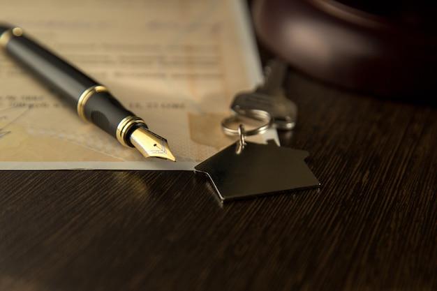 Huurcontract. een huurovereenkomst / leasedocument met sleutels en pen.sleutels op het ondertekende koop- en verkoopcontract van het huis en het handvat