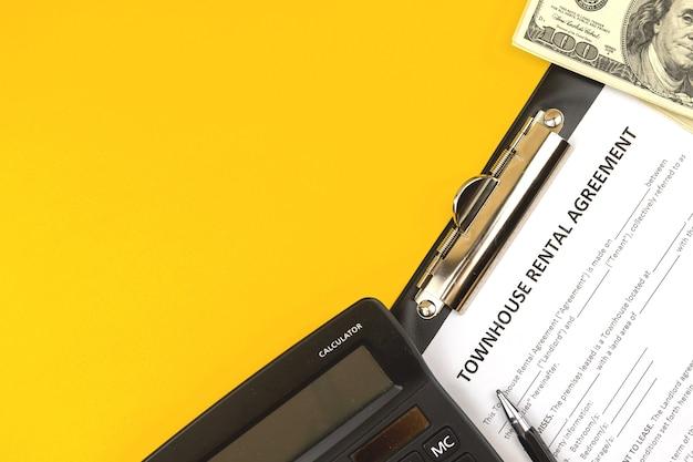 Huurovereenkomst huurwoning. office-bureaublad met rekenmachine, pen en geld. bovenaanzicht foto en kopieer ruimte