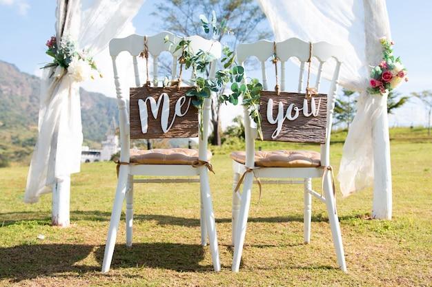 Huwelijk me en u ondertekent op stoelen die zich in het hout bevinden.
