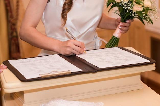 Huwelijk ondertekening register, pen en officieel document bruidspaar vasthouden