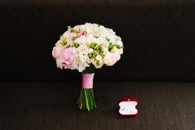 Huwelijks bruids boeket en rode doos met trouwringen op bruine aark
