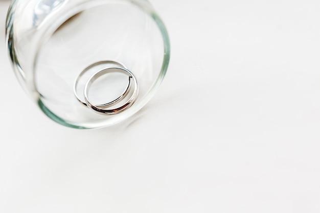 Huwelijks gouden ringen in transparant glas. symbool van liefde en huwelijk.