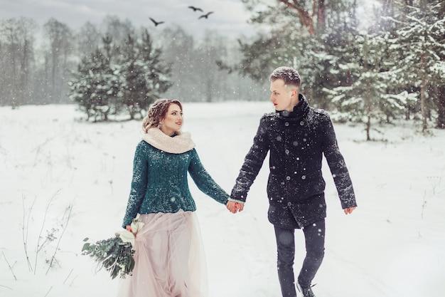 Huwelijks kaukasisch paar in wintertijd dicht omhooggaand portret in openlucht. liefdevolle schattige tedere paar verliefd samen wandelen in opzichtige bos
