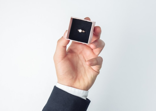 Huwelijksaanzoek. man's handen met een geschenkdoos met een gouden diamanten ring op een wit
