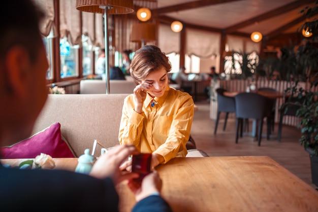 Huwelijksaanzoek met trouwring aan mooie vrouw bij luxerestaurant. paar romantische date