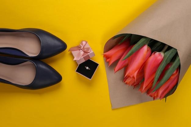 Huwelijksaanzoek. tulpenboeket, gouden ring met diamant in geschenkdoos, hakschoenen op geel