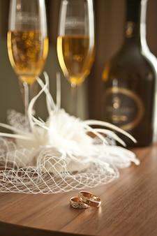 Huwelijksattributen liggen bij hoed- of sluierglazen en flessen champagne