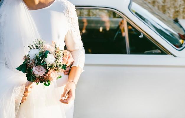 Huwelijksauto met bloemen en bruid met boeket van bloemen in haar hand