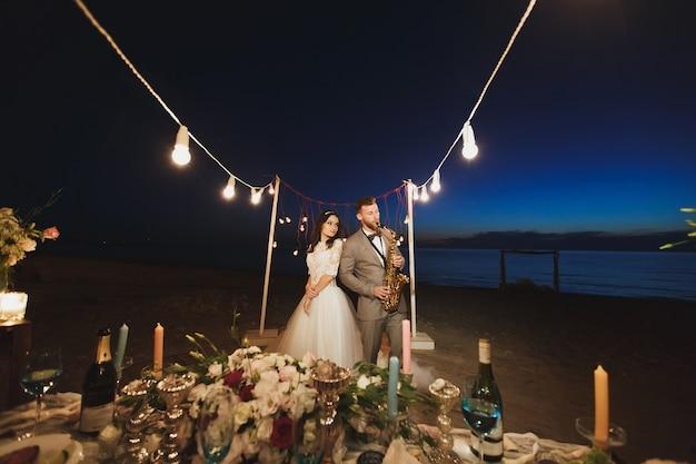 Huwelijksbanket op de oceaankust bij nacht. de bruidegom speelt saxofoon.
