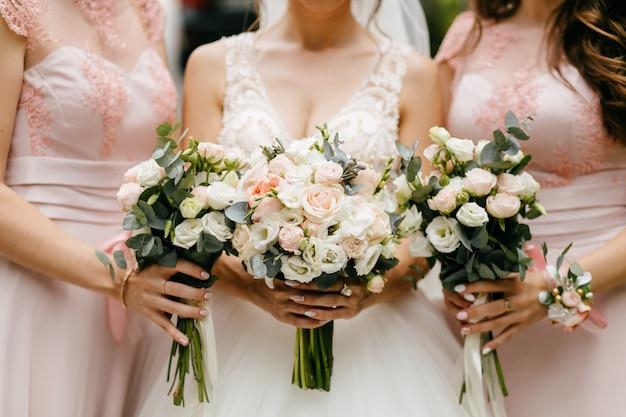 Huwelijksbloemen, bruid en bruidsmeisjes die hun boeketten houden bij huwelijksdag