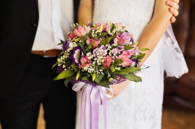 Huwelijksbloemen, huwelijksboeket, de bruid en bruidegomzitting naast het bruidmeisje die een bruids boeket van roze houden