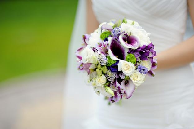 Huwelijksboeket bij de handen van de bruid