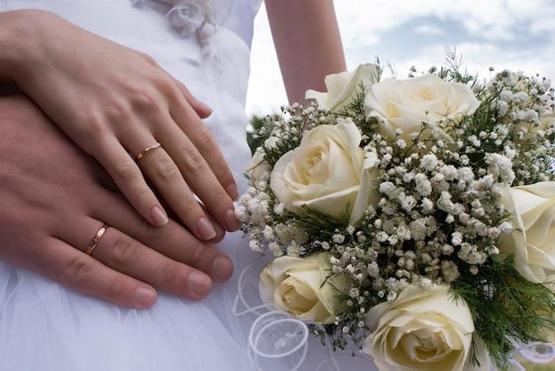 Huwelijksboeket en handen met ringen