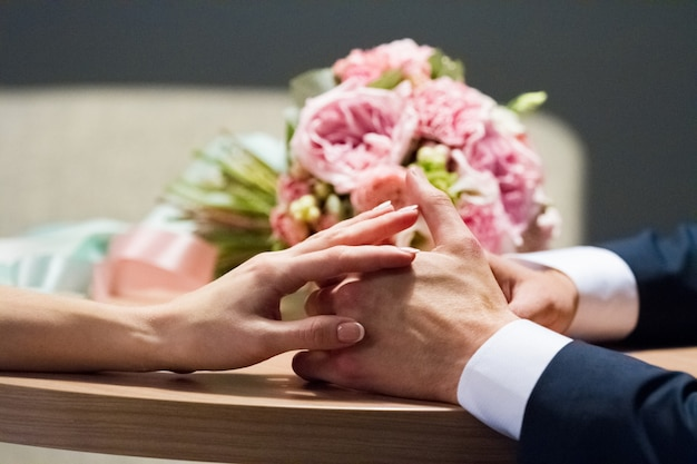 Huwelijksboeket en handen van de bruid en de bruidegom