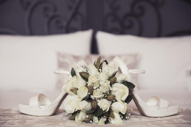 Huwelijksboeket en schoenen op slaapkamer