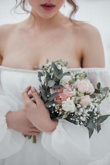 Huwelijksboeket in de handen van de bruid. fotograferen in de winter