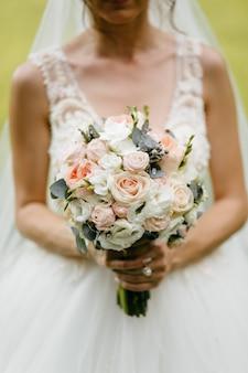 Huwelijksboeket in de handen van de bruid