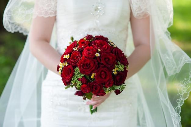 Huwelijksboeket in de handen van de bruid.
