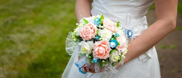 Huwelijksboeket in handen van de bruid op de achtergrond van groen gras