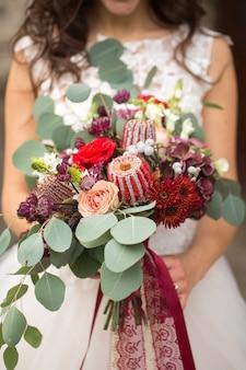 Huwelijksboeket in handen van de bruid