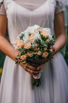 Huwelijksboeket met oranje rozen in de handen van de bruid met een ring