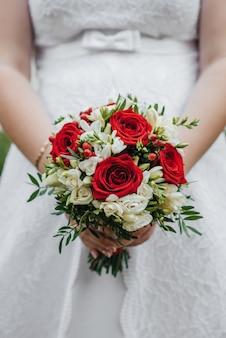 Huwelijksboeket met rode en witte rozen in de handen van de bruid