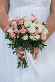 Huwelijksboeket met roze en witte rozen in de handen van de bruid