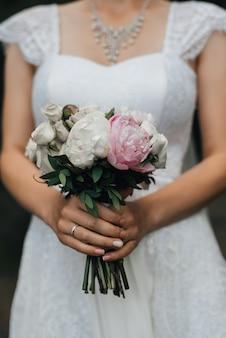 Huwelijksboeket met roze pioenen en witte rozen in de handen van de bruid
