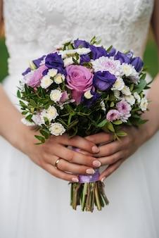 Huwelijksboeket met roze rozen en witte chrysanten in de handen van de bruid
