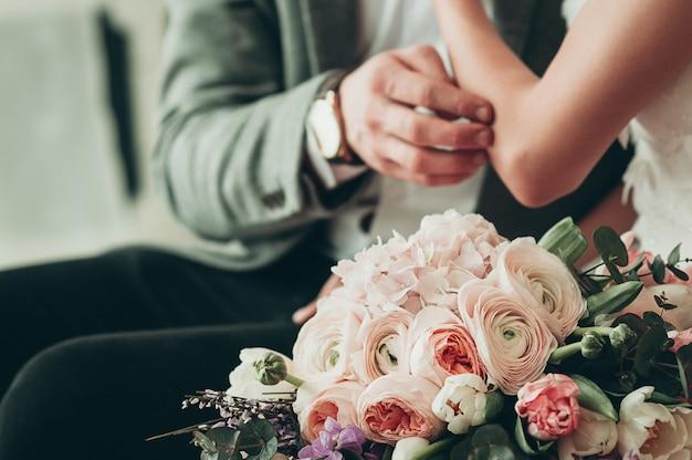Huwelijksboeket met vage bruid en bruidegom