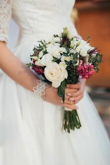 Huwelijksboeket met witte rozen in de handen van de bruid