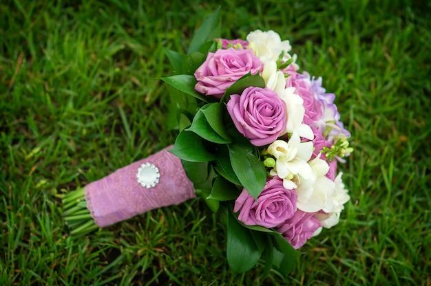 Huwelijksboeket van bloemen die op groen gras liggen