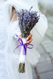 Huwelijksboeket van lavendel in de handen van vrouwen.