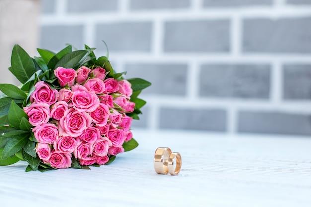 Huwelijksboeket van roze rozen en trouwringen. ruimte kopiëren. de