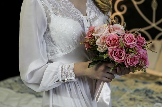 Huwelijksboeket van roze rozen in de handen van de verzamelende bruid