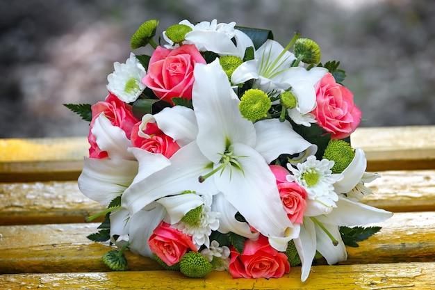Huwelijksboeket van rozen en lelies voor bruid op een huwelijksfeest.