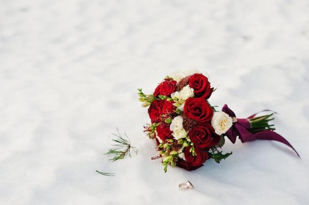 Huwelijksboeket van witte en rode rozen op sneeuw.