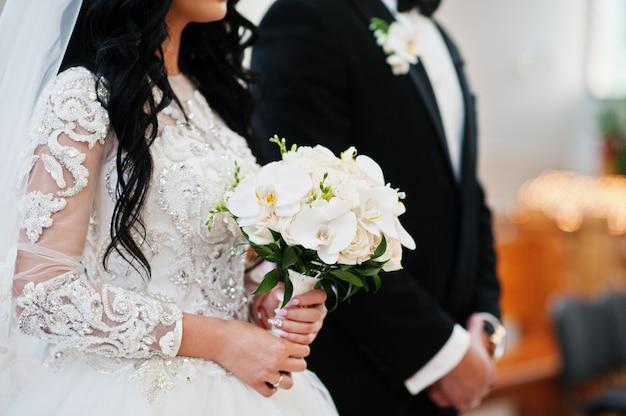 Huwelijksboeket van witte orchideeën op hand van bruid op kerkceremonie