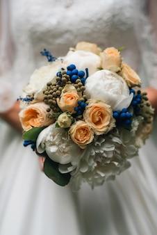 Huwelijksboeket van witte pioenen en gele rozen in de handen van de bruid