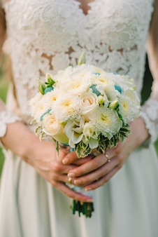Huwelijksboeket van witte rozen in handenbruid