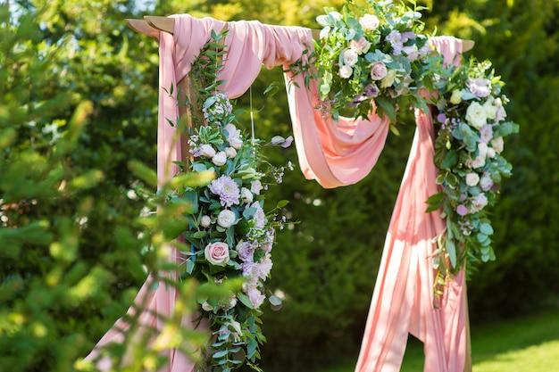 Huwelijksboog gemaakt van verse bloemen en stof