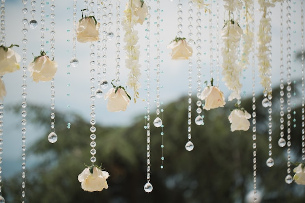 Huwelijksboog met bloemen en kralen op blauwe hemel close-up.