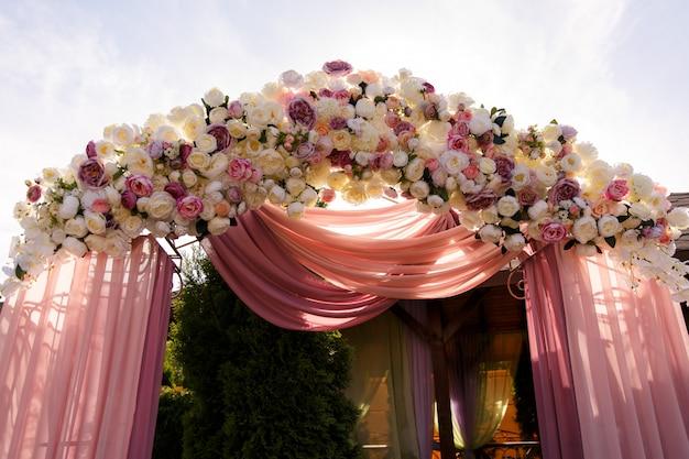 Huwelijksboog met verse en kunstbloemen voor huwelijksceremonie