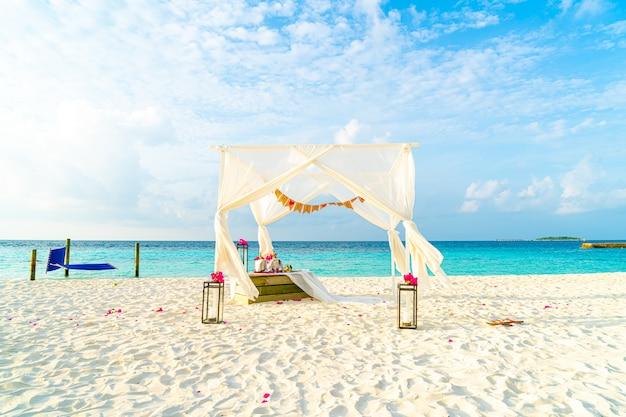 Huwelijksboog op strand met tropische maldiven resort en zee